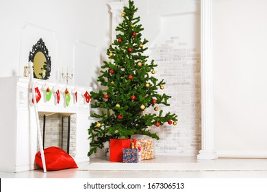 Decorated fir tree and gift boxes near fireplace in living room