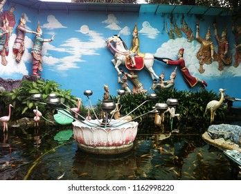 decorated fish pond and fortune bowls inside the Dhammikarama Burmese Buddhist temple in Penang, Malaysia