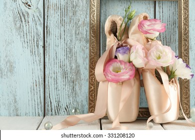 Decorated with flowers ballet shoes in frame on blue wooden background