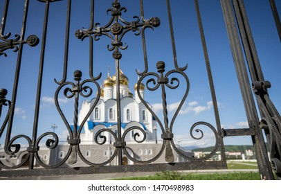Decorated forged fence around the Trinity Cathedral in Petropavlovsk-Kamchatsky. The largest and most impressive church, golden-domed stunner, visible from all over the city. Russia, Kamchatka.