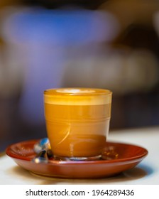 decorated glass of Coffee Piccolo Latte on a white table in a Sydney Cafe NSW Australia