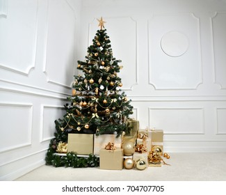 Decorated gold Christmas tree with golder patchwork ornament artificial star hearts presents for new year in rich house on white background