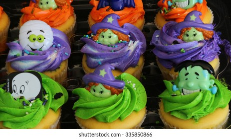 Decorated Halloween cupcakes on black background