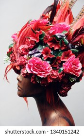 Decorated head of mannequin with hair, flowers and feathers, grey studio background