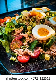 decorated healthy good looking tuna salad with eggs, tomatoes and cucumbers on an elegant black plate