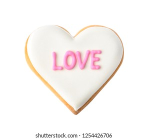 Decorated heart shaped cookie with word LOVE on white background, top view. Valentine's day treat