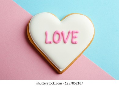 Decorated heart shaped cookie with word LOVE on color background, top view. Valentine's day treat