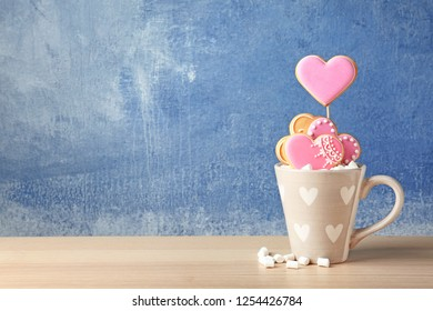 Decorated heart shaped cookies in cup on table. Space for text