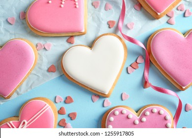 Decorated heart shaped cookies on color background, flat lay