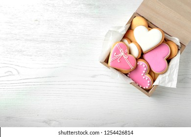 Decorated heart shaped cookies in wooden box and space for text on table, top view