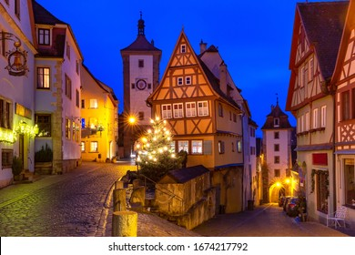 Decorated and illuminated Christmas street with gate and tower Plonlein in medieval Old Town of Rothenburg ob der Tauber, Bavaria, southern Germany