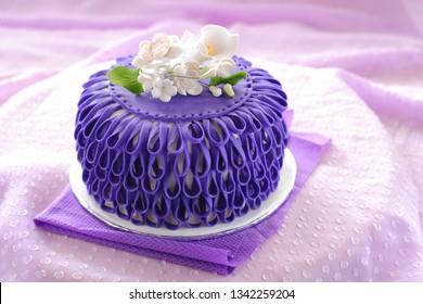 Decorated novelty cake: white flower bouquet on purple ruffle cake
