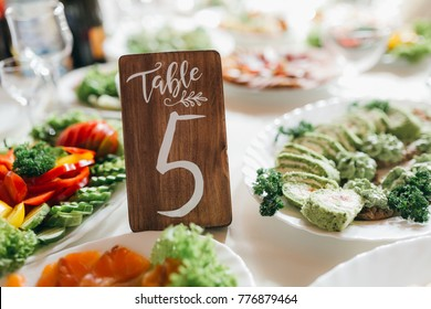 Decorated and numbered wedding table with food, drink, appliances and flowers.
