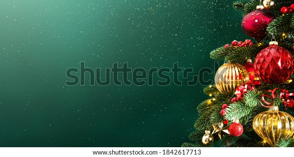 Decorated with ornaments and lights Christmas tree on dark green background. Merry Christmas and Happy Holidays greeting card, frame, banner. New Year. Noel. Winter holiday theme.