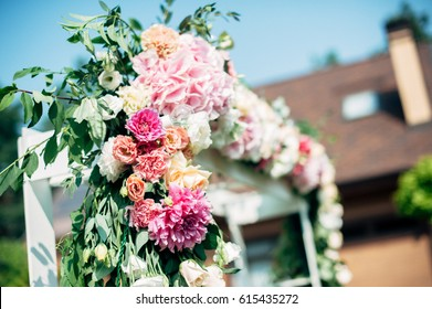 decorated outdoor wooden wedding arch with white, pink and red flowers