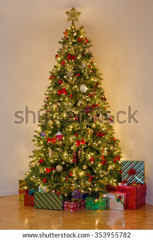 decorated pine tree with many presents under it room lit only by yellow christmas tree