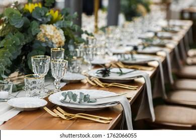 Platos decorados con tenedor y cuchara. Mesa de estilo boho con pampas y vegetación