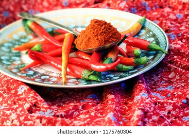 A decorated plate with red peperoni and spices.
