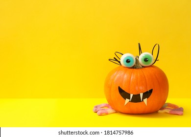 Decorated pumpkin with candy eyes on yellow background
