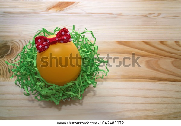 decorated with red bow egg in nest with space for text on wooden background