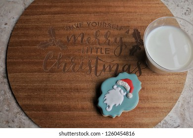 Decorated Santa's sugar cookie and cup of milk on Have Yourself a Merry Little Christmas wooden board