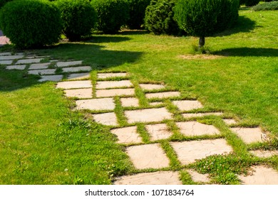 decorated stone paths among shrubs and flower beds in landscape design