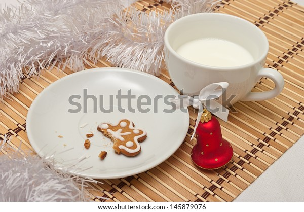 Decorated Sugar Cookies and Milk for Santa at Christmas Time on a table with decoration