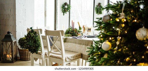 Decorated table waiting for guests and Christmas tree