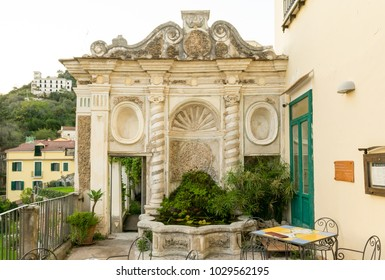 A decorated vintage styled wall in the Minerva garden in Salerno, Italy. In the bottom left there is a little door wich takes to the botanical garden