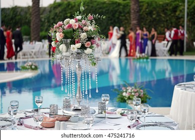 Decorated wedding table near the swimming pool.Bride ,groom and bridesmaids blurry at the background.