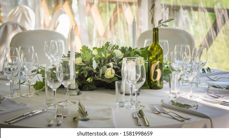 Decorated wedding tables with numbers on bottles and beautiful rose compositions on the tables