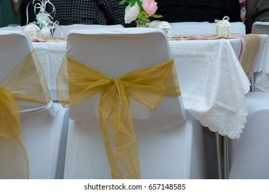 decorated white wedding chair with golden now tied around the back. decorative detail at wedding reception.