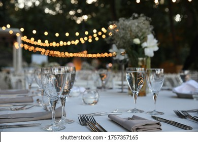 Decorated white wedding table for a festive dinner with pink flowers in brass pots on green lawn under the open sky.
