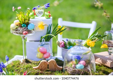 Decorated wooden table in the Easter theme with Easter eggs, moss, flowers in the open air