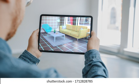 Decorating Apartment: Man Holding Digital Tablet with AR Interior Design Software Chooses 3D Furniture for Home. Man is Choosing Sofa, Table for Living Room. Over Shoulder Screen Shot with 3D Render