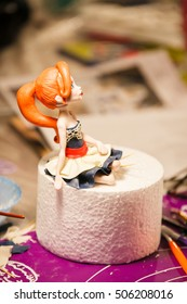 decorating cake. doll with red hair. figure on children's cake