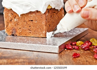 Decorating cake with a pastry bag full of cream