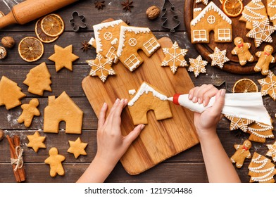 Decorating Christmas bakery. Woman glazing homemade gingerbread cookies on kitchen table, top view