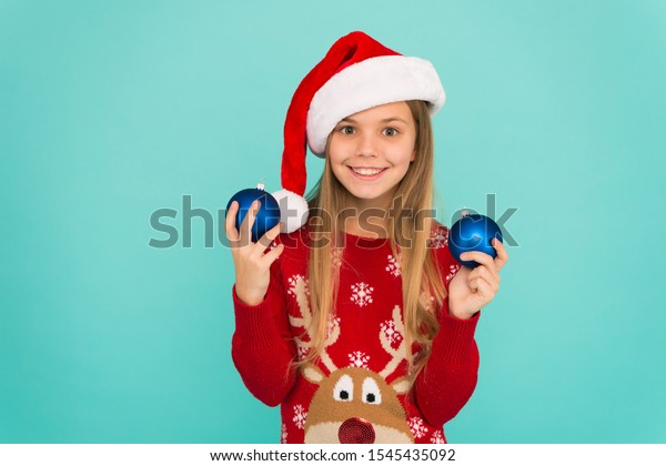 Decorating christmas tree. Girl smiling face hold balls ornaments blue background. Let kid decorate christmas tree. Favorite part decorating. Add more decorations. Getting child involved decorating.