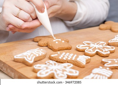 Decorating gingerbread cookies (bear) with white icing, selective focus and place for text