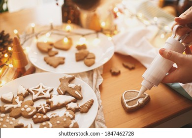 Decorating gingerbread cookies with icing on rustic table with lights. Christmas holiday tradition and advent. Hands decorating baked christmas cookies with sugar frosting. Family time - Shutterstock ID 1847462728