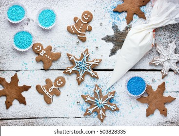 Decorating gingerbread man and snowflake Christmas cookie background, Christmas treats for kids cooking process concept