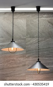 Decorating industrial lamps made off metal in cone shape and against stone wall tiles
