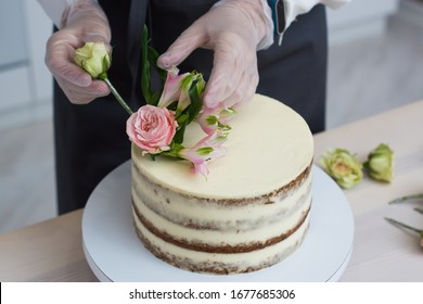 Decorating naked cake on a turntable with live flowers of pink and green color on a white kitchen