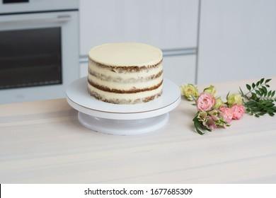nackter Kuchen auf einem Tisch mit Blumen in Rosa und Grün auf einer weißen Küche