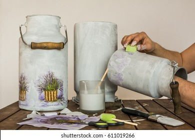 Decorating old milk churns with lavender pattern - decoupage accessories (brush, scissors, tissues, sponge, paint) and hands of an artist on a table.