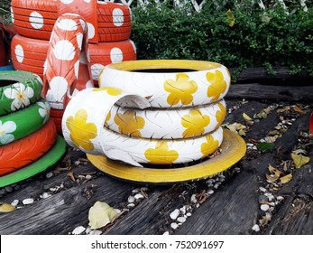 Decorating the old tire wheels as a cup of tea or coffee for copping plants with colorful and warm creative recycling in the garden background