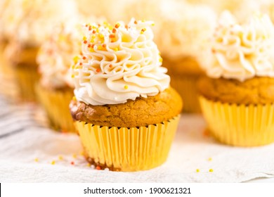 Decorating pumpkin spice cupcake with Italian buttercream and sprinkles.