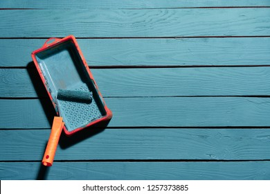 Decorating and renovation concept. Paint roller brush in a tray with blue paint on wooden planks.