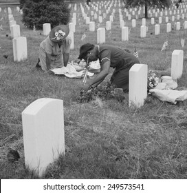 Decorating a soldier's grave on Memorial Day in one of the African American sections. Arlington National Cemetery, Virginia. May 1943.
